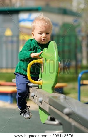 Portrait of toddler child outdoors. One year old baby boy wearing green sweater at playground seesaw