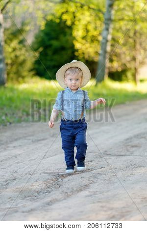 Portrait of toddler child outdoors. Rural scene with one year old baby boy with straw hat