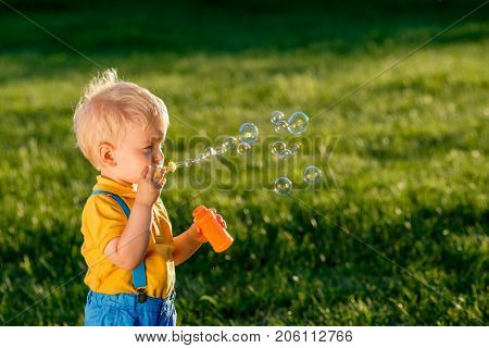 Portrait of toddler child outdoors. Rural scene with one year old baby boy blowing soap bubbles. Healthy preschool children summer activity. Kid playing outside.