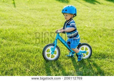 Boy in helmet riding a blue balance bike (run bike). Happy child learning to keep balance on a training bicycle in the garden. Healthy preschool children summer activity. First day on the bike.