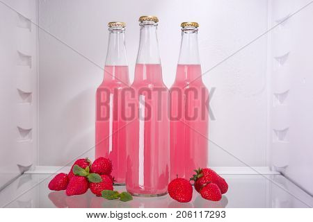 Bottles of fresh strawberry lemonade in fridge