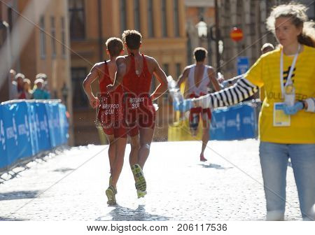 STOCKHOLM - AUG 26 2017: Rear view of running triathlete Fridelance and Briford in the old town in Stockholm in the Men's ITU World Triathlon series event August 26 2017 in Stockholm Sweden