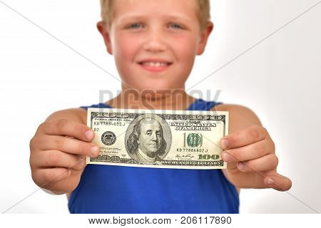 A subsidy for a child. A boy holds money in his hands. Helping children's shelters.