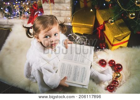 Happy baby girl reading book with fairy tales. Decorated Cristmas tree. New Year 2018. Merry Christmas