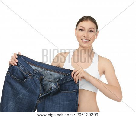 Beautiful young woman with oversized jeans on white background. Diet concept