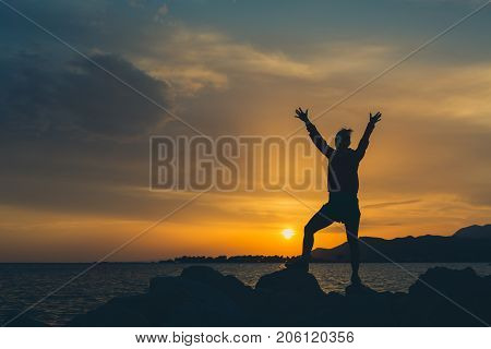 Girl with arms outstretched at a seaside. Beautiful inspiring landscape and sea with girl and hands raised on sunset Croatia.
