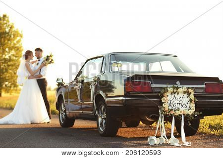 Car with plate JUST MARRIED and happy wedding couple outdoors