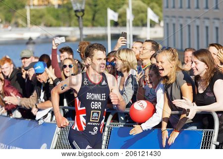 STOCKHOLM - AUG 26 2017: Running triathletes Jonathan Brownlee and smiling hand clapping girls in the background in the Men's ITU World Triathlon series event August 26 2017 in Stockholm Sweden