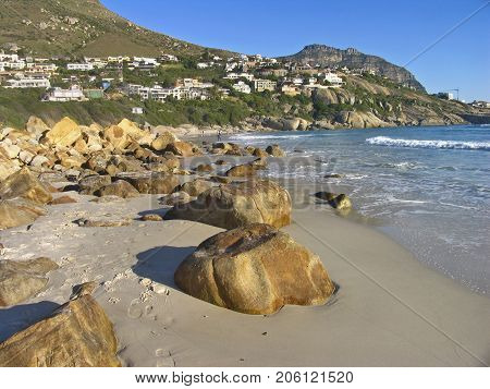 A LANDSCAPE, WITH HUGE ROCKS ACROSS THE BEACH  IN THE FORE GROUND AND A MOUNTAIN IN THE BACK GROUND