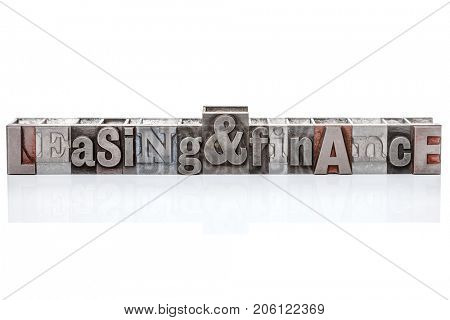 The words Leasing and Finance made from old metal letterpress typeset, isolated on a white background with reflection.