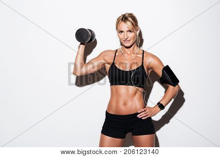 Pretty smiling sportswoman in earphones and armband standing and holding dumbbell and looking at camera isolated over white background poster