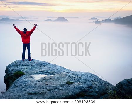 Tall Tourist Celebrate On The Peak Of The World . Orange Thick Fog Bellow In Deep Valley. Dreamy Day