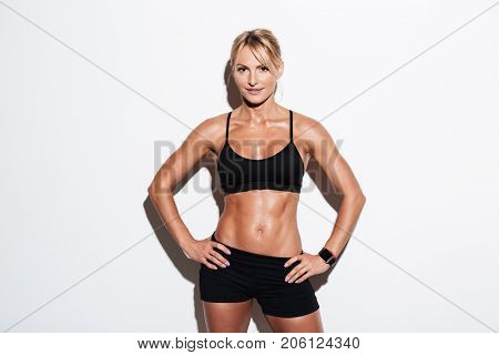 Smiling pretty athlete woman posing while standing with hands on hips isolated over white background