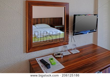 Mirror and wooden commode in bedroom