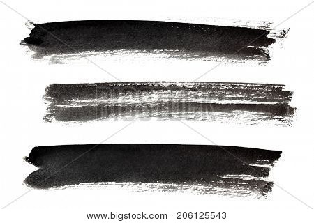Set of long ink black brush strokes isolated on the white background