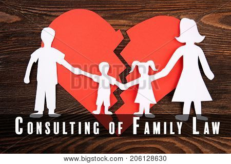 Paper figures of parents with children and broken heart on wooden background. Consulting of family law
