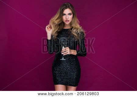 Attractive sexy young woman in sexy short brilliant dress with glass of champagne in studio on pink background