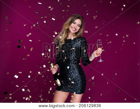 Portrait of attractive smiling girl with tinsel confetti in hands bottle of champange and wineglasses with champagne. New year's feeling. Merry christmas. Happy woman celebrate holiday