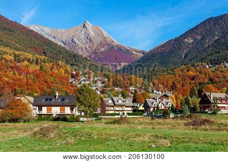 View of green field and small village as colorful autumnal mountains on background under blue sky in Switzerland.