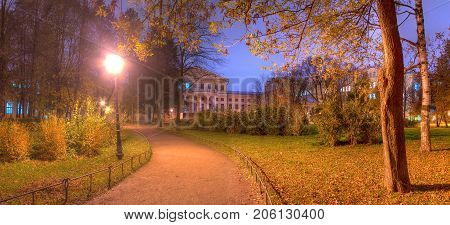 Panoramic night view of park footpath and building of State University of Communication in Yusupov Garden Saint Petersburg Russia