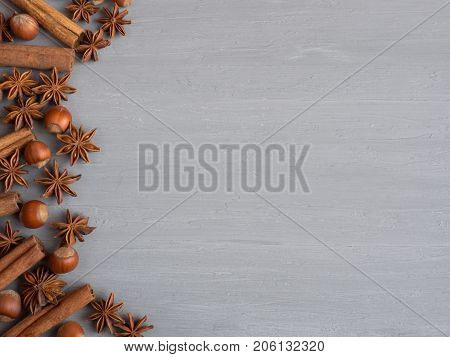 Cinnamon sticks spice star hazelnuts on a light background the concrete Free space