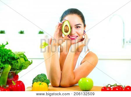 Beauty young Funny woman holding fresh avocado. vegetables, tomatoes. Smiling in her kitchen. Healthy eating concept. Diet, dieting, slimming, weight loss. Beautiful girl Cooking. Healthy Lifestyle