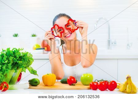 Beauty young funny woman holding fresh vegetables- peppers and smiling in her kitchen at home. Healthy eating concept. Diet, dieting, slimming, weight loss. Young Woman Cooking. Healthy Lifestyle