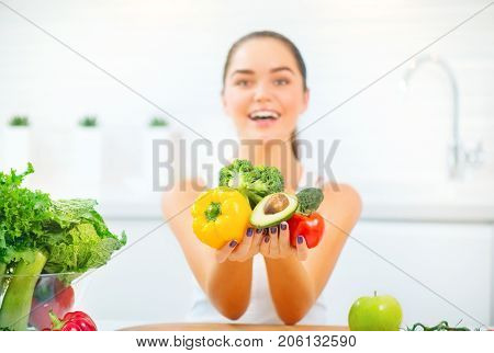 Beauty young woman holding fresh vegetables and fruits and smiling in her kitchen at home. Healthy eating concept. Diet, dieting, slimming, weight loss. Young Woman Cooking. Healthy Lifestyle