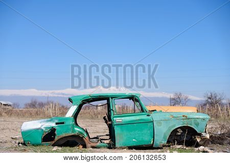 ARARAT PROVINCE, ARMENIA - APRIL 4: Russian car in the middle of dry agricultural land with scenic snow-topped mountains and clear blue sky on the background April 4, 2017 in Ararat Province, Armenia.