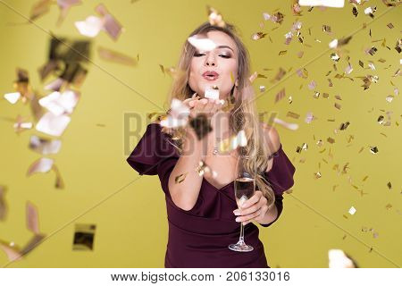Beautiful young woman with champagne amuse and dancing. Girl blows off sequins. Happy New Year