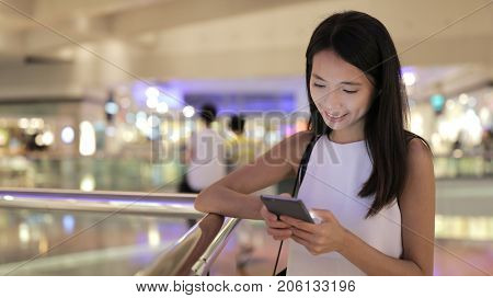Young Woman using cellphone in shopping mall