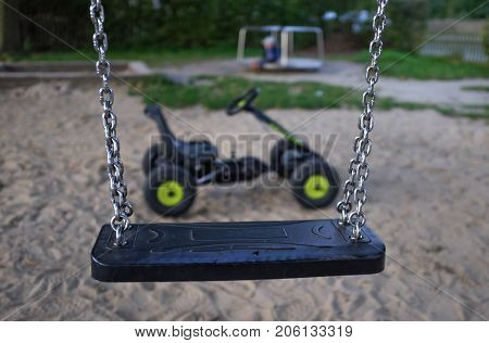 A children's swing with a pedal car and playground in the background