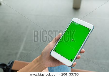 Woman holding mobile phone with green chroma key