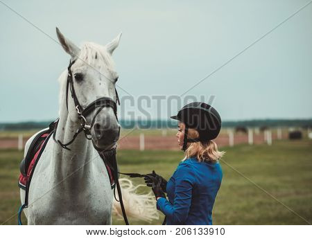 Middle-aged woman with her horse outdoors