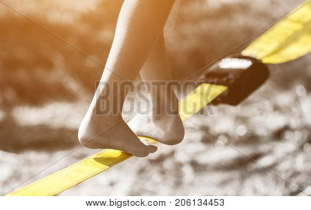 Tightrope walker is on a tight sling which is fixed on the trees at a low altitude. Slasklining extreme sport a balancing act.