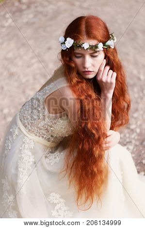 Portrait of a beautiful redheaded girl with long curly hair. Bride. With handmade jewelry on the hair. Hair to the waist. Very long red hair. The average plan