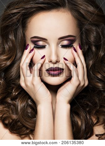 Beautiful face of  young woman with maroon makeup and nails
