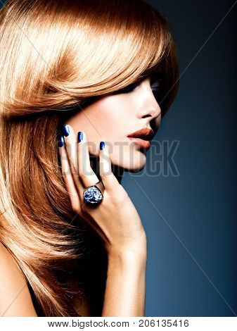 Face of a beautiful woman with sapphire jewelry ring on finger. Portrait  of young fashion model with blue eye makeup