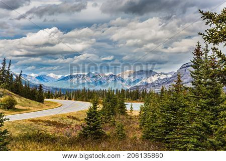 The road to distant snow-capped mountains in the Rockies of Canada. Rocks and lakes under flying clouds. Concept of active and ecological tourism