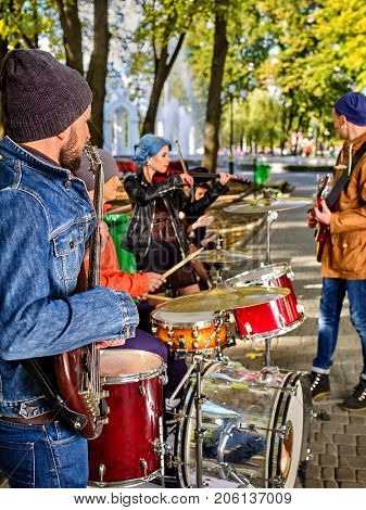 Festival music band in autumn park. Hands playing on percussion instruments in city park . Drums with sticks closeup of male musicians. People like street music.