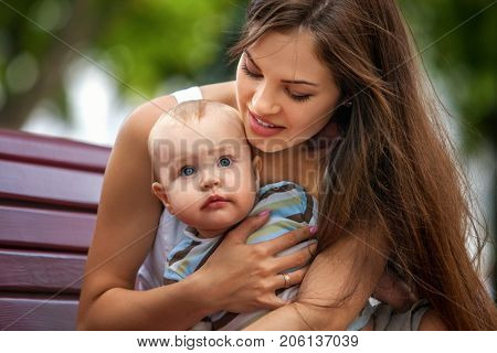 Baby in park outdoor. Kid on mom's hands. Happy beautiful mom and child summer on city outside. Portrait of happy loving mother and her son spring outdoors. Adoption of child.