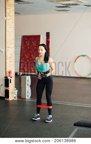 cute fit girl performs modern leg exercises with elastic rubber