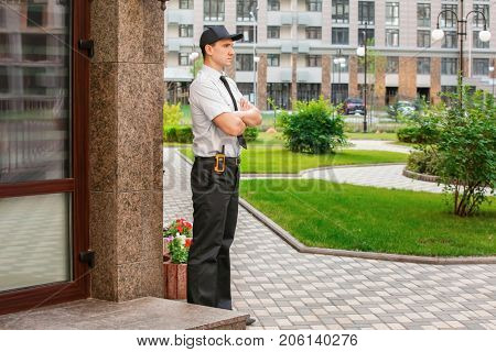 Male security guard near building, outdoors