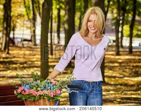 Woman on bicycle with flowers basket is riding autumn park outdoor in shiny sunlight on light background. Girl is happily walking in park in fall.