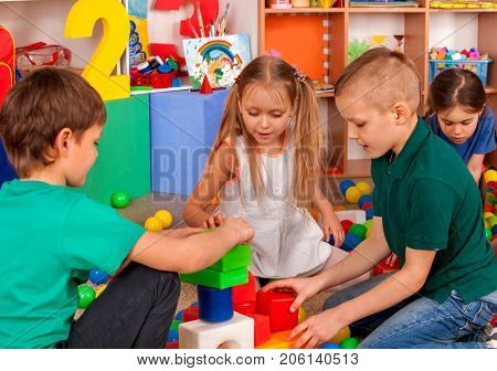 Children building blocks in kindergarten. Group kids playing toy on floor. Top view of interior preschool. Building a tower of cubes. Logical constructor.