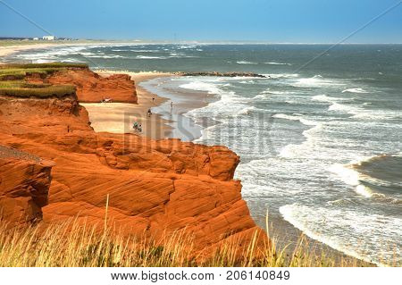 Red cliff in Havre aux maisons with waves in the ocean in the St-Lawrence golfe