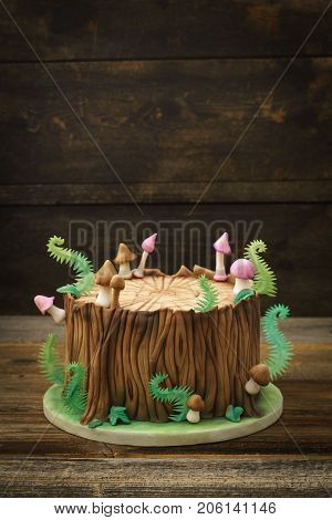Enchanted forest woodland themed fondant cake with a tree trunk, ferns, mushrooms and leaves on wooden background with copyspace