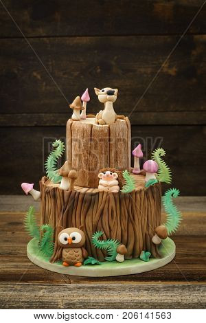 Enchanted forest woodland themed fondant cake with a hedgehog, deer, owl, tree trunk, ferns, mushrooms and leaves on wooden background