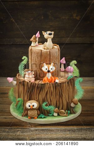 Enchanted forest woodland themed fondant cake with a hedgehog, deer, owl, fox, snail, tree trunk, ferns, mushrooms and leaves on wooden background