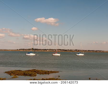 Close Up Of Three Boats Moored In River On Bright Sunny Day